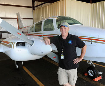 BANGOR, ME -- SEPTEMBER 21, 2015 -- Gary Soucy, image specialist and pilot with Down East Emergency Medical Institute, stands next to the late 1970s model Grumman Cougar twin engine plane that was donated to DEEMI by Doug Kell of Ellsworth.